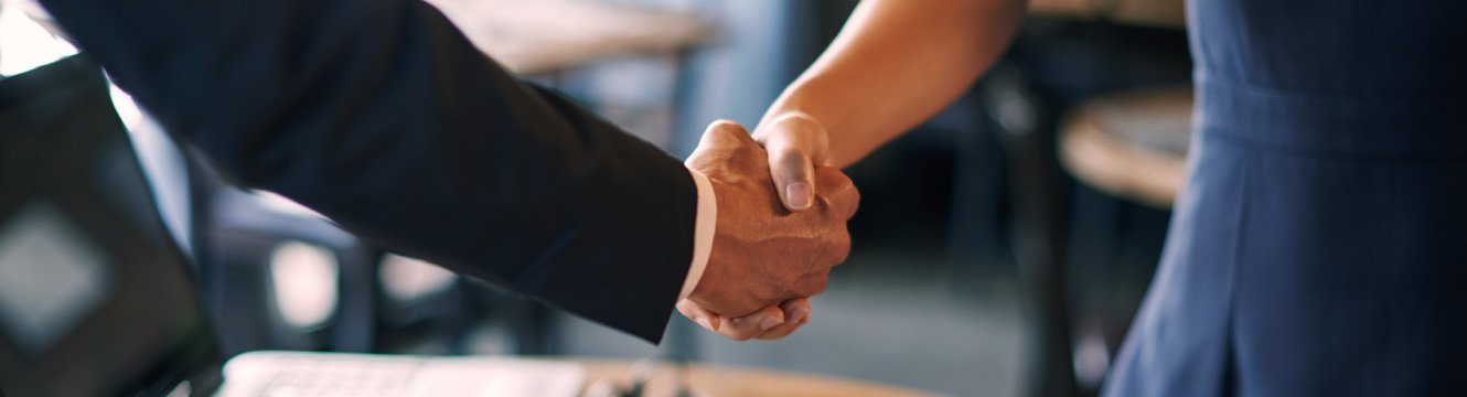 A business woman and man shaking hands