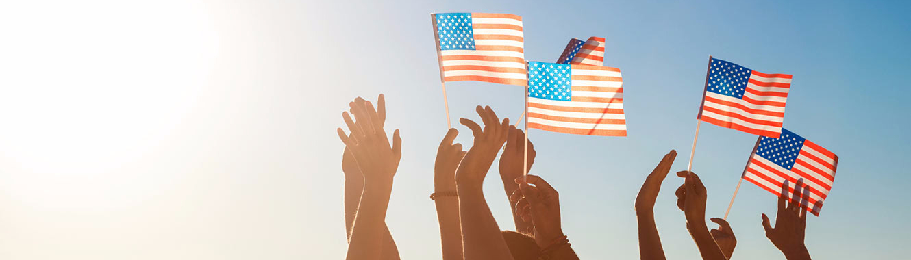 people with their hands in the air holding American flags